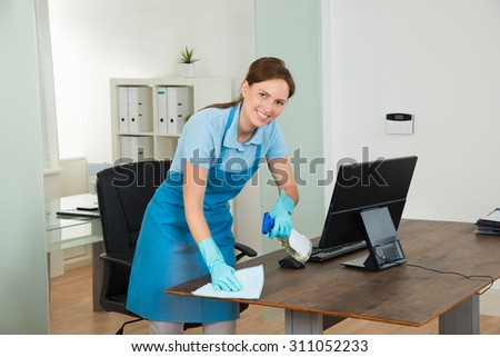 Young Happy Female Janitor Cleaning Wooden Desk With Rag In Office - stock photo