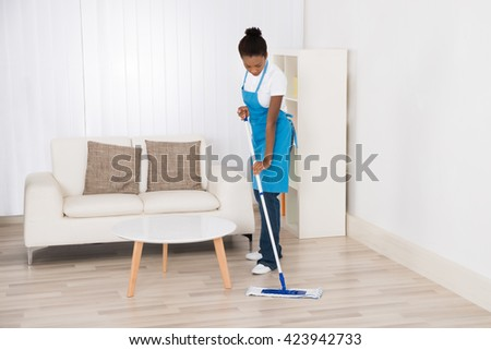 Young Happy Female Janitor Mopping Floor In Room - stock photo