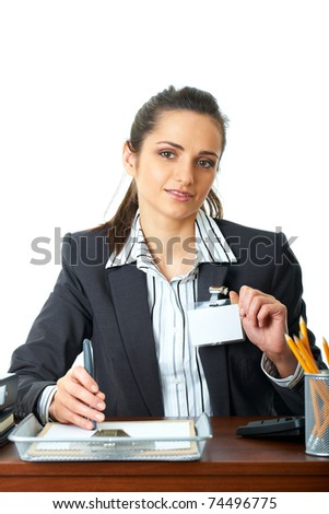 young happy female office worker sits at her desk, holds her id badge, isolated on white background - stock photo