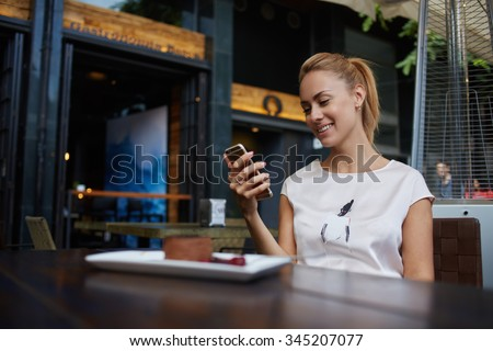 Young happy female reading good news on her mobile phone while sitting in modern coffee shop interior, gorgeous hipster girl with beautiful smile watching funny video on cell telephone during lunch  - stock photo