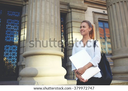 Young happy female student holding closed laptop computer after defense of diploma in University, smiling woman traveler with net-book in hands decides where to go next while standing near museum - stock photo