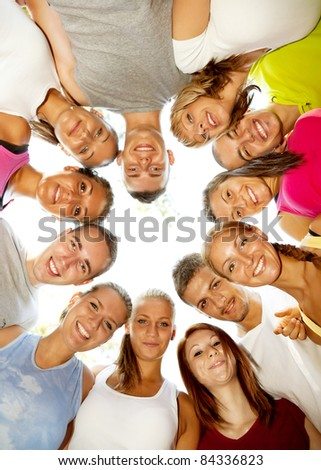 young happy friends with heads together in circle - stock photo