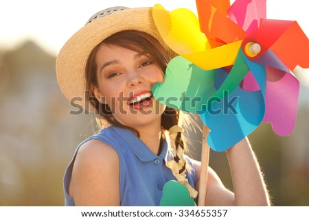 Young happy funny (vintage) dressed woman close-up  with colorful weather vane,looking like flower