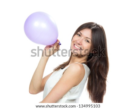 Young happy girl blowing balloons for birthday party smiling and looking at the camera on a white background - stock photo