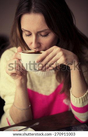 Young happy girl drinking hot coffee or tea sits in a cafe, lifestyle, breakfast or lunch enjoys relaxing, healthy lifestyle, fashion, in a yellow sweater. - stock photo