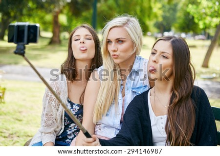 young happy girl friends sitting on park bench taking selflie photos with mobile cell phone on stick - stock photo