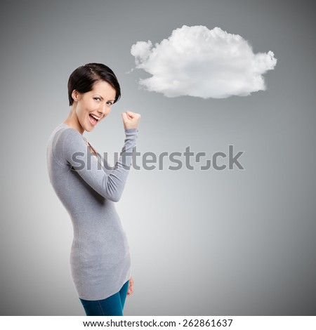 Young happy girl gestures fist on grey background - stock photo