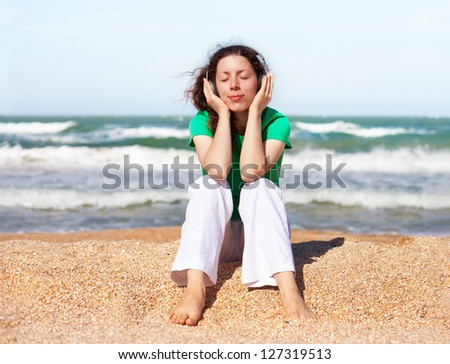 Young happy girl listening to music with headphones while sitting on the beach - stock photo