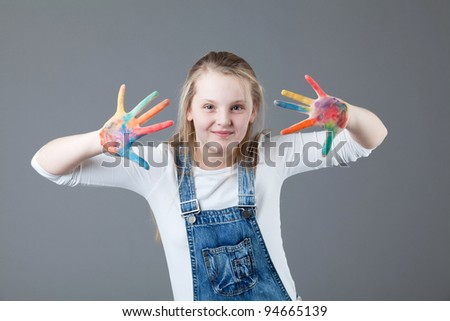 young happy girl.  little girl on a gray background. hands in the paint. - stock photo