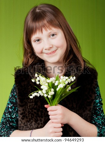 young happy girl.  little girl on green background. girl with flowers. - stock photo