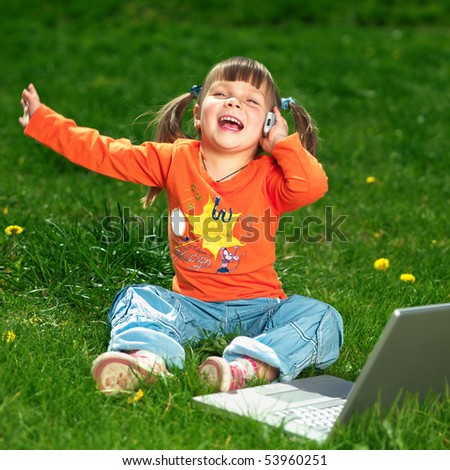 young happy girl on the grass with laptop - stock photo