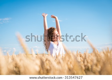 Young happy girl running and jumping carefree with open arms over wheat field. Toned image. Selective focus. - stock photo