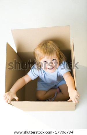Young happy girl sitting in cardboard box. She's looking at camera. High angle view. - stock photo
