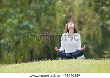 young happy girl training yoga on sunny meadow - stock photo