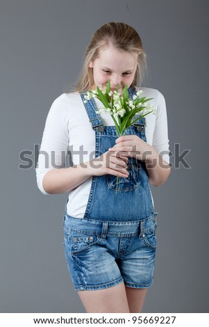 young happy girl with flowers.   little girl on a gray background - stock photo
