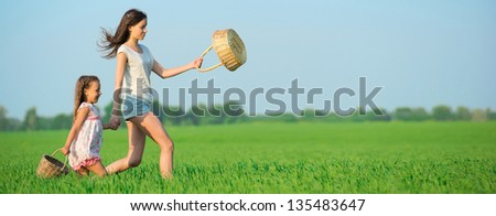 Young happy girls running with basket at green wheat field with her friend together - stock photo
