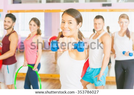 Young happy group people of women and men lead a healthy lifestyle, exercise in fitness room. Exercise strengthens a person physically and make them more happy! Asian woman training with weight - stock photo