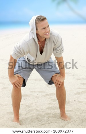 Young happy guy having fun on the beach with nice smile and barefeet in the sand - stock photo