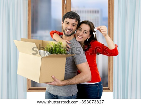 young happy Hispanic couple moving together in a new flat or apartment carrying cardboard boxes home belongings holding house key smiling in housing and real state concept - stock photo