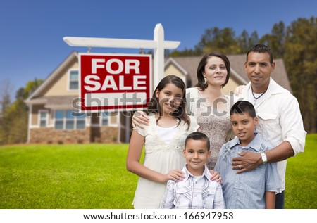 Young Happy Hispanic Young Family in Front of Their New Home and For Sale Real Estate Sign. - stock photo