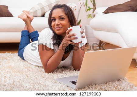 Young happy indian lying down on the floor woman using a laptop - stock photo