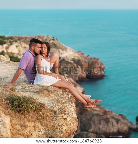 Young happy interracial couplesitting on a mountain near the ocean - stock photo