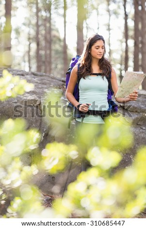 Young happy jogger looking at map in the nature - stock photo
