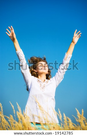 Young happy jumping woman. On blue sky background. - stock photo