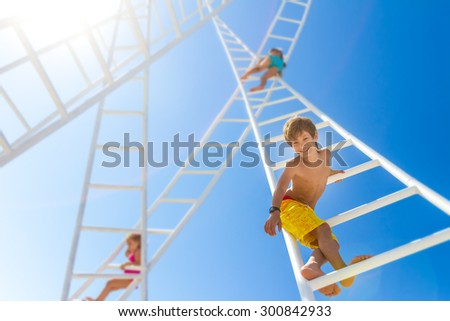 young happy kids - boy and girl - climbing white ladders going nowhere up on natural sky background, outdoor - stock photo