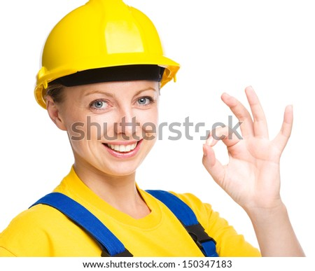 Young happy lady as a construction worker is showing OK sign, isolated over white - stock photo