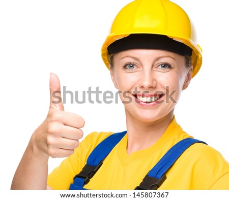 Young happy lady as a construction worker is showing thumb up sign, isolated over white - stock photo