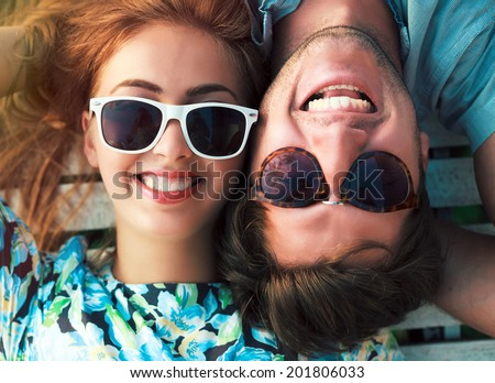 Young happy laughing and smiling couple in love posing outdoor in summer time at bright vintage clothes and sunglasses. - stock photo