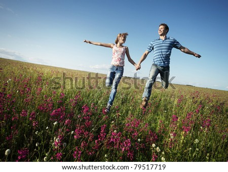 Young happy lovers running on meadow with green grass and pink flowers on a blue sky - stock photo
