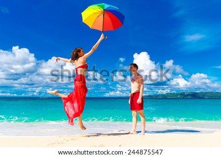 young happy loving couple having fun in the tropical beach with multicolored umbrella  - stock photo