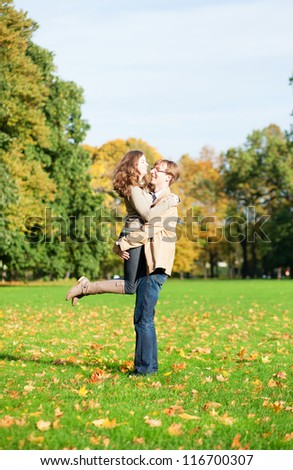 Young happy loving couple having fun on a fall day - stock photo
