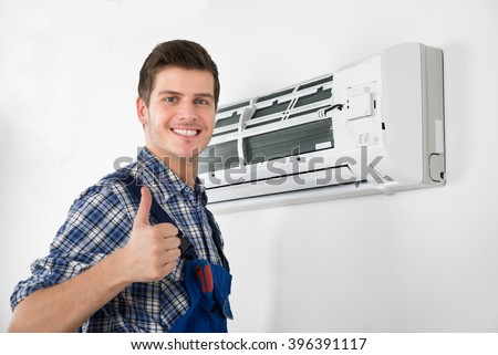 Young Happy Male Technician Gesturing Thumb Up - stock photo