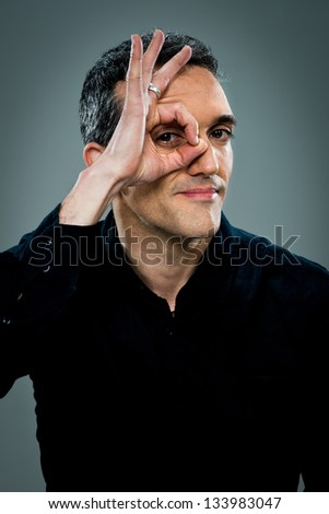 Young Happy Man Doing OK Sign with His Eye Over a Grey Background - stock photo