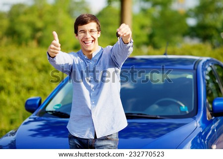 Young happy man in glasses standing in front of his new car and showing thumb up and car key - stock photo