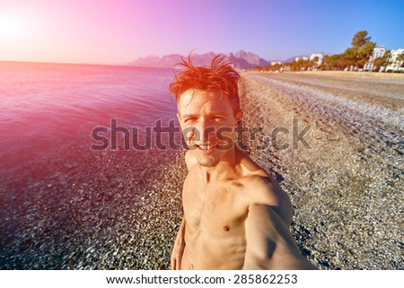 young happy man make selfie on the beach.  - stock photo