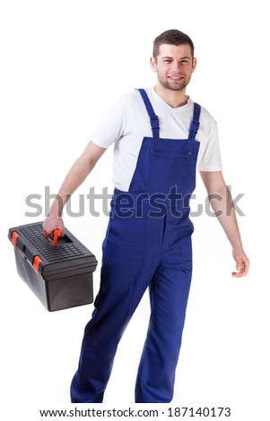 Young happy man standing and holding toolbox - stock photo