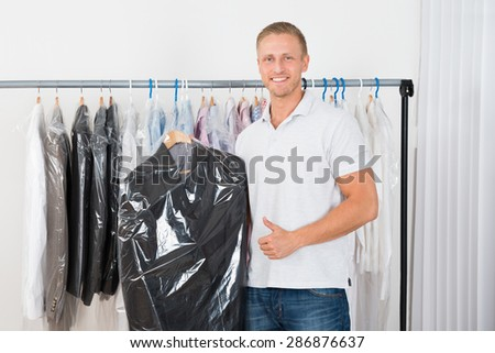 Young Happy Man Standing With Coat In Dry Cleaning Store - stock photo