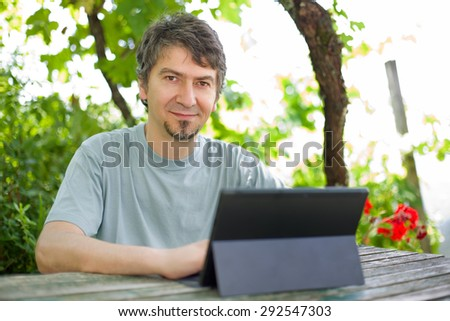 young happy man with a tablet pc, outdoor - stock photo
