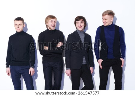 Young happy men standing near white wall, laughing - stock photo
