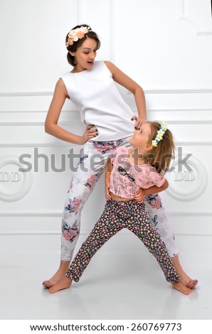 Young happy mother and four years old daughter laughing together smiling yelling screaming in the room on a white background - stock photo