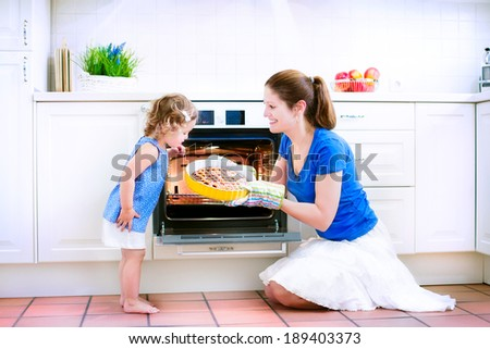 Young happy mother and her adorable curly toddler daughter wearing blue dress baking a pie together in an oven in a white sunny kitchen with modern appliances and devices - stock photo