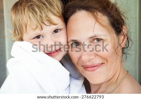 Young happy mother and her cute baby girl in white towel after taking a bath, closeup portrait with selective focus - stock photo