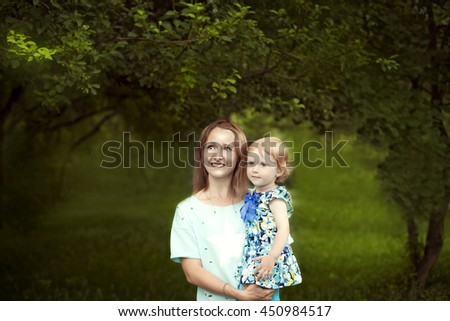 young happy mother holding her baby girl in her arms and smiling in summer Park outdoors - stock photo