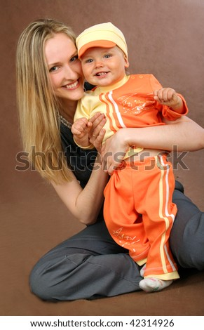 Young happy mother with baby in  orange suit on brown background - stock photo