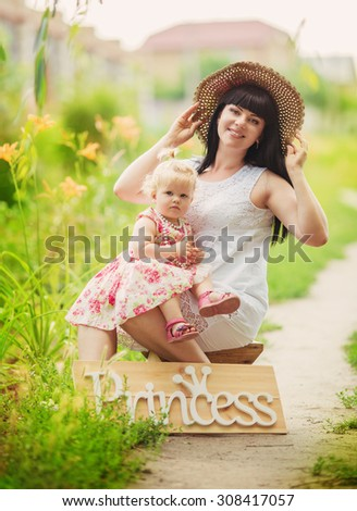 Young happy mother with baby in park - stock photo