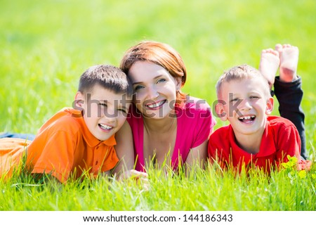 Young happy mother with children in park -  outdoor portrait - stock photo